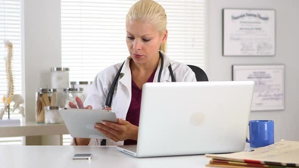Thumbnail for Female doctor working on tablet and laptop computer