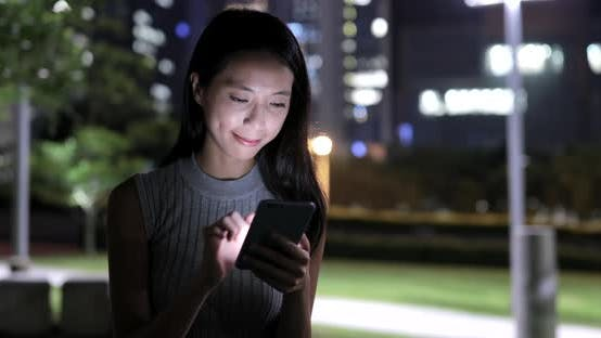 Cover Image for Woman using mobile phone in city at night