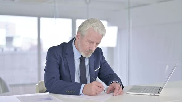 Disappointed Old Businessman Trying To Write on Paper