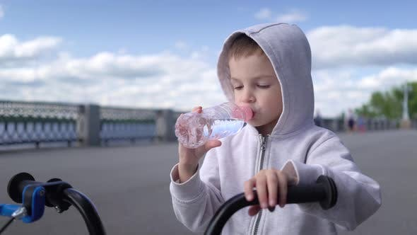 Thumbnail for Cute 3 - 4 Years Boy Child Learning To Ride First Running Balance Bike and Drink Water