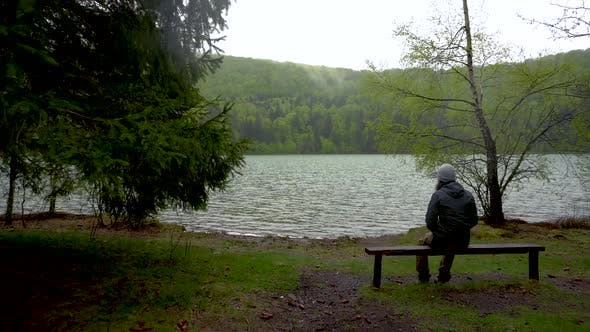 Enigmatic lonely man sitting on bench on lake shore in the mountain forest. Lake Sf. Ana Romania