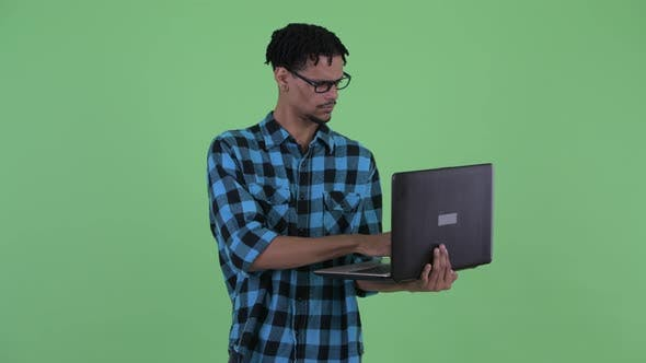 Thumbnail for Happy Young African Hipster Man Thinking While Using Laptop