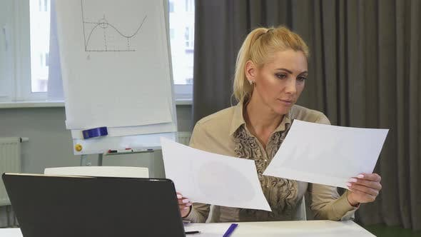 Thumbnail for Mature Business Woman Looking Confused While Examining Documents