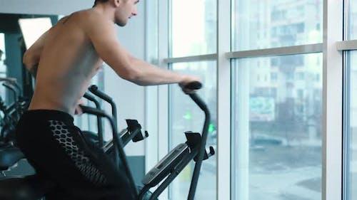Junger Mann trägt Training kaum auf Radmaschine