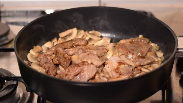 Cooking Pork with Mushrooms. Chef Preparing Delicious Pork Lunch.