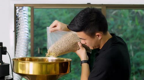 Asian Man Pouring Coffee Beans Into The Roaster Machine
