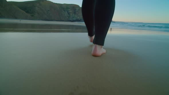 Camera Follows Barefoot Surfer in Wetsuit on Beach