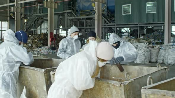Workers Sorting Garbage at Recycling Facility