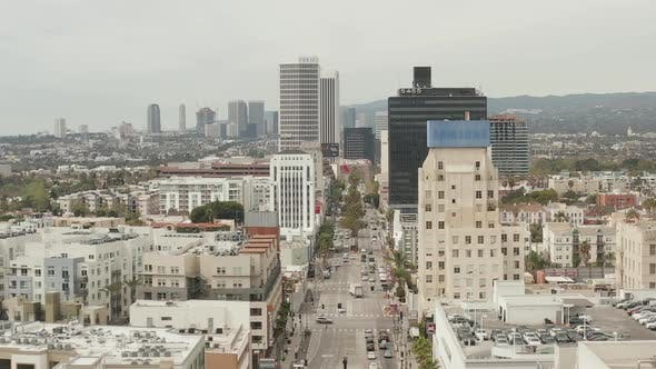 Cover Image for AERIAL: Flight Over Wilshire Boulevard Close To Street and Buildings with Car Traffic in Los Angeles