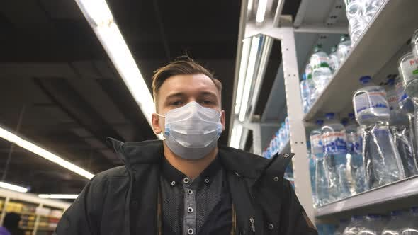 Thumbnail for Portrait of Young Man with Medical Face Mask Walking at Supermarket. Guy Going at Shop with