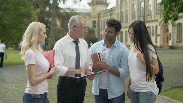 Professor Giving Assignments to Group of Multi-Ethnic Students Education
