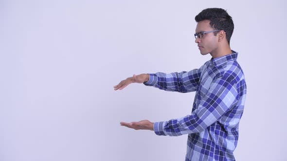 Happy Young Indian Hipster Man Snapping Fingers and Showing Something