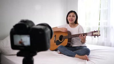 Asian female blogger playing acoustic guitar and recording video