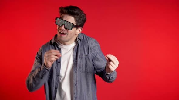 Thumbnail for Handsome Man with Glowing Disco Glasses Dancing Isolated on Red Background.