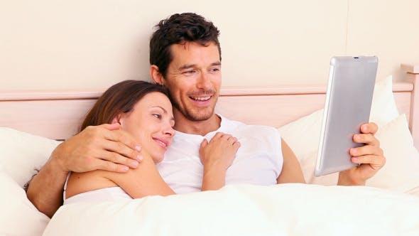 Thumbnail for Paar liegend im Bett mit digitalem Tablet