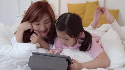 grandma happy relax with young girl before bedtime lying on bed in bedroom.