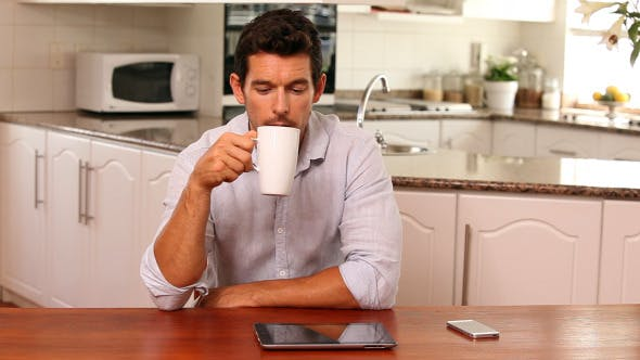 Handsome Man Using Tablet Pc At The Table