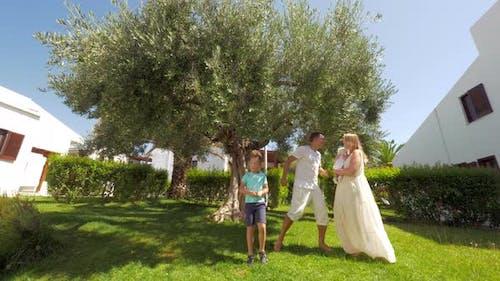 Happy parents with kids dancing in the garden