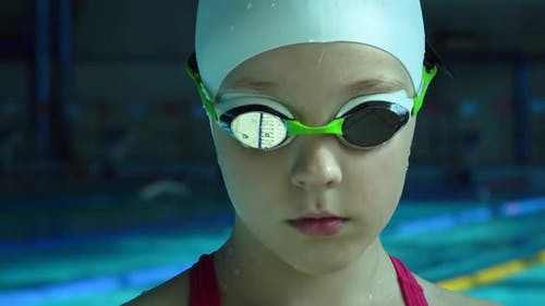 Teenager Girl in Goggles Looking at Camera in Swimming Pool, Close Up