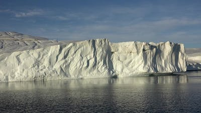 Sailing along the ice cliff of a glacier reaching the sea. Icebergs