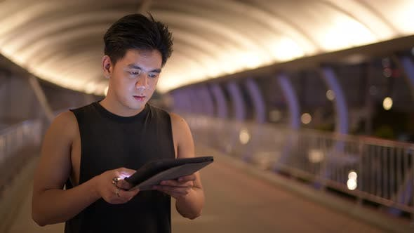 Thumbnail for Portrait of Young Handsome Asian Man Thinking While Using Digital Tablet Outdoors at Night