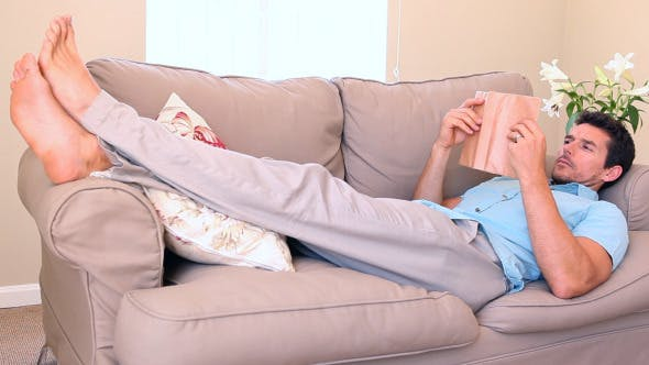 Man Lying On Couch Falling Asleep While Reading