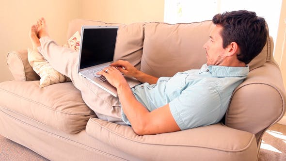 Thumbnail for Man Lying On Couch Typing On Laptop