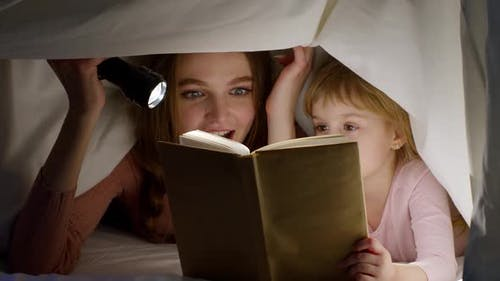 Mother and Daughter Lying in Bed at Home Under Duvet Blanket and Reading Bedtime Stories Fairytales