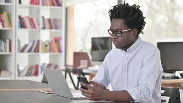 Thumbnail for African Man Using Smartphone and Laptop