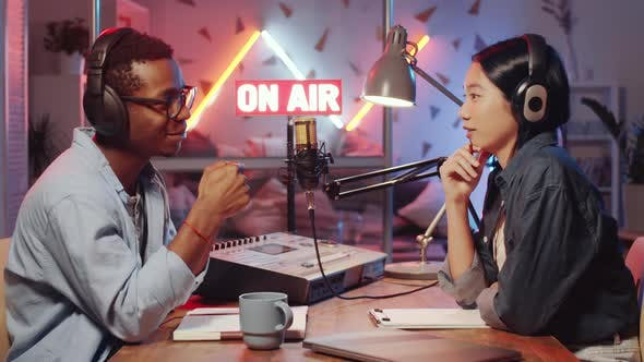 Multiethnic Man and Woman Recording Podcast in Radio Studio