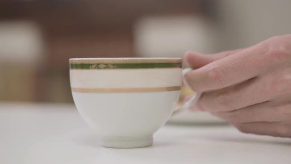 Thumbnail for Close-up of White Cup with Tea or Coffee Standing at the Table. Adult Male Caucasian Hand Taking It