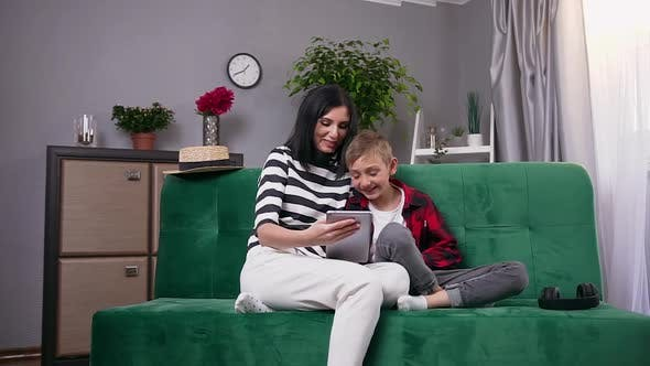 Thumbnail for Mother and Son which Spending their Leisure Together at Watching Funny Cartoon or Video on Tablet PC