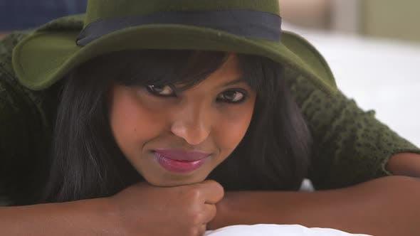Thumbnail for Black girl wearing floppy hat on bed