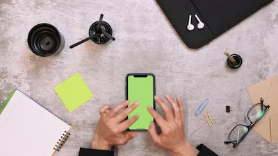Smartphone with chroma key green screen on table
