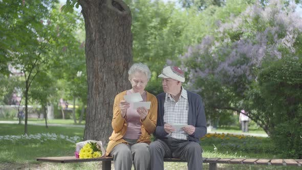 Thumbnail for Portrait Cute Adult Couple Looking Old Photos Remembering Happy Moments Sitting on a Bench in the