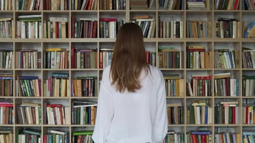 Young Woman Student Reading a Book in a Library