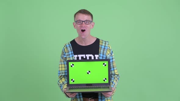 Thumbnail for Portrait of Happy Nerd Man Showing Laptop and Looking Surprised