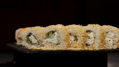 Sushi Sprinkled With Sesame Seeds And Wrapped In Salmon Laid Out On A Black Board.