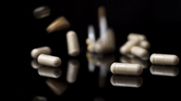 Thumbnail for Pills Drugs Capsules Fall Down and Fly Around on the White Surface. Slow Motion