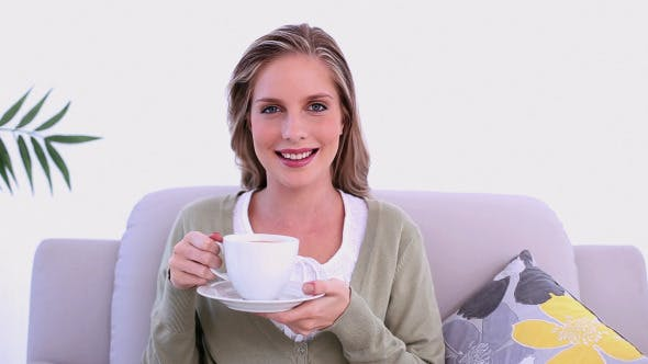 Thumbnail for Content Woman Drinking From Cup Sitting On Couch