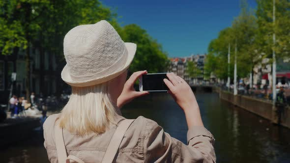 Cover Image for Using a Smartphone, a Woman Takes a Beautiful View of the Canal in Amsterdam