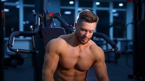 Bodybuilder ohne Hemd im Fitnessstudio. Gutaussehender Mann mit Muskeln posiert in der Turnhalle in die Kamera