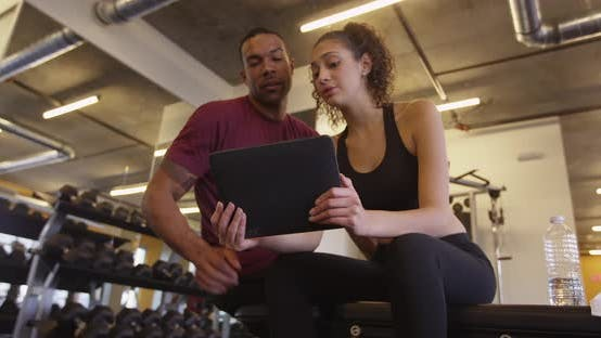 Thumbnail for Happy fit Black and Hispanic couple using tablet computer in gym