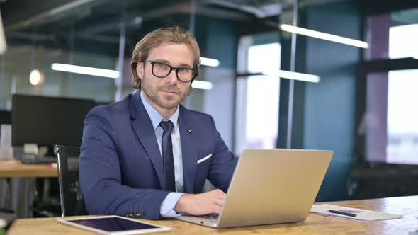 Cover Image for Cheerful Businessman Showing Thumbs Up at Work