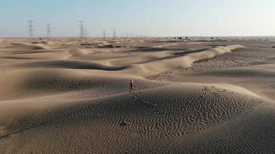 Landscape View on the Great Sandy Desert in UAE with a Woman Walking on Sand