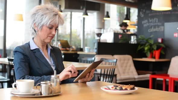 Thumbnail for Business Middle Aged Woman Works on Tablet in Cafe - Coffee and Cake