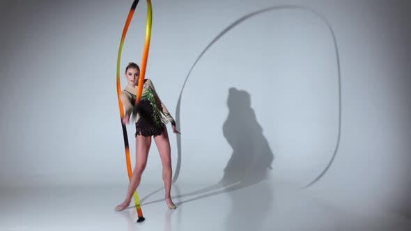 Thumbnail for Rhythmic Gymnast Doing Acrobatic Moves with the Tape. White Background. Slow Motion