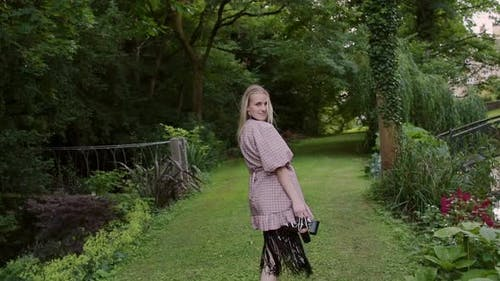 Lovely Woman Fashion Model In Barefoot Looks Back At The Camera As She Walks Through Lush Green Lawn