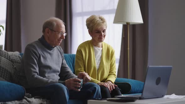 Happy Grandmother and Grandfather are Chatting By Online Video Chat in Laptop with Friends or Family