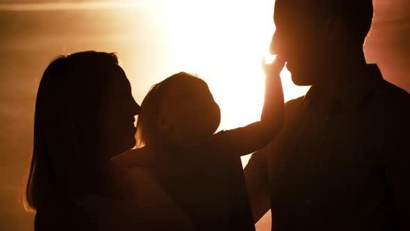 Couple Hugging Toddler at Sunset